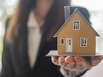 Realtor holding a small model house